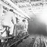 Mijnwerkers op een mijnfiets op de gemoderniseerde 105 meter verdieping van de Willem Sophia Mijn