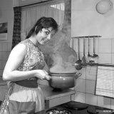 Vrouw aan fornuis in de keuken