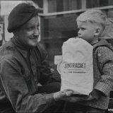 Mijnwerker met kind bij nieuwe papieren zak gevuld met syntraciet
