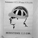 Affiche met de tekst ' tussen helm en Kruin minstens twee en een halve centimeter'
