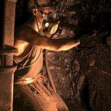 Mijnwerker met afbouwhamer in pijler