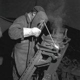 Arbeider last de beide slothelften en de rugplaat van een Gerlachstijl aan elkaar