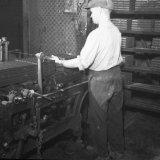 Steenafnemer Collard aan het afsnijapparaat in de steenfabriek van de Staatsmijn Maurits