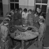 Een groep OVS'ers van Troep 12 van de Staatsmijn Hendrik bij een tafel met uitgestald mijnmateriaal