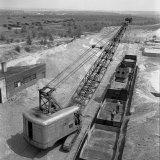 Het lossen van zand en grind bij de betonblokkenfabriek gebeurt met behulp van een grote grijperkraan