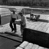 Het laden van betonblokken op wagons voor transport naar de diverse Staatsmijnen