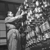 Bedieningsman J. Vondelhoff neemt een benzinelamp uit een uitgifterek in de nieuwe Lampisterie van de Staatsmijn Emma