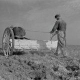 Boer bezig met het strooien van kunstmest