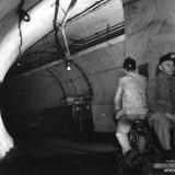 Arbeiders per mijnfiets op weg naar de schacht op de 700 meter verdieping van de Staatsmijn Emma