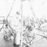 Ploegleider W. Tiesch (staande op de voorgrond)  instrueert tijdens het troepwerk een sjorring aan zijn OVS ploegleden