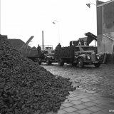 Het beladen van vrachtwagens bij de kolenopslag