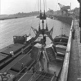 Een kubel met kunstmest die met een grote kraan van een wagon is afgenomen wordt boven het schip open getrokken